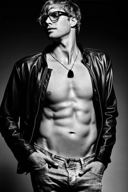 Jovem bonito musculoso cabe homem modelo masculino posando no estúdio, mostrando seus músculos abdominais na jaqueta de couro Foto gratuita