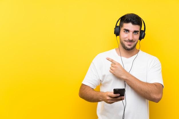 Jovem bonito ouvir música com um celular na parede amarela, apontando para o lado para apresentar um produto Foto Premium