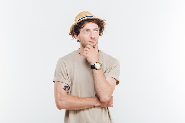 Jovem bonito pensativo em pé pensando sobre um fundo branco Foto Premium