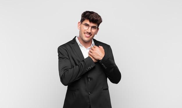 Jovem bonito se apaixonando e parecendo fofo, adorável e feliz, sorrindo romanticamente com as mãos ao lado do rosto Foto Premium