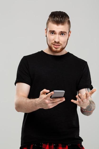 Jovem bonito segurando o telefone sobre parede cinza. Foto gratuita