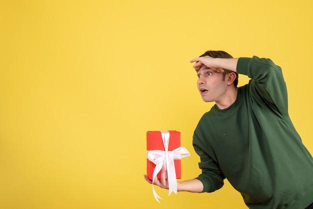 Jovem bonito segurando um presente de frente e olhando para algo amarelo Foto gratuita