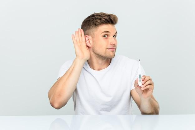 Jovem bonito segurando um termômetro tentando ouvir uma fofoca. Foto Premium