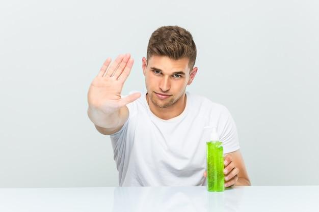Jovem bonito segurando uma garrafa de aloe vera em pé com a mão estendida, mostrando o sinal de stop, impedindo-o. Foto Premium