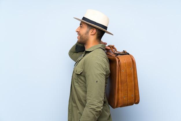 Jovem bonito, segurando uma mala vintage Foto Premium