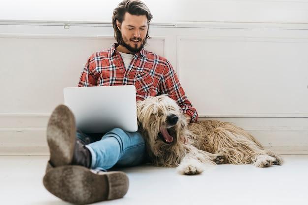Jovem bonito sentado no chão com cachorro usando laptop Foto gratuita