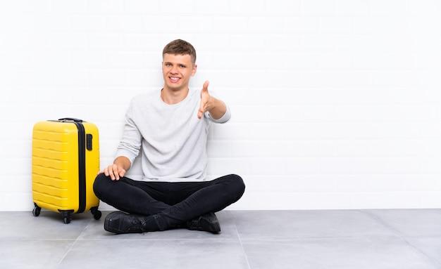 Jovem bonito sentado no chão com um aperto de mão mala depois de um bom negócio Foto Premium
