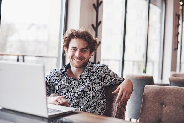 Jovem bonito sentado no escritório com uma xícara de café e trabalhando no projeto conectado com as modernas tecnologias cibernéticas Foto Premium