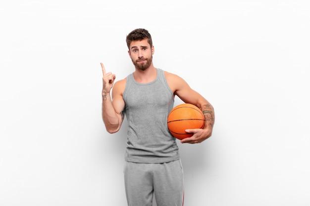 Jovem bonito, sentindo-se um gênio segurando o dedo orgulhosamente no ar depois de perceber uma ótima idéia, dizendo eureka segurando uma bola de basquete Foto Premium