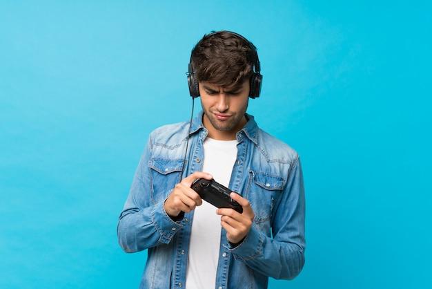 Jovem bonito sobre azul isolado jogando em videogame Foto Premium