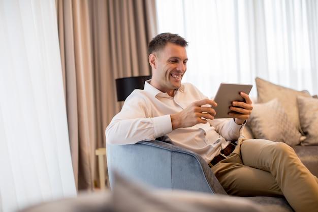 Jovem bonito usando tablet digital em apartamento de luxo Foto Premium