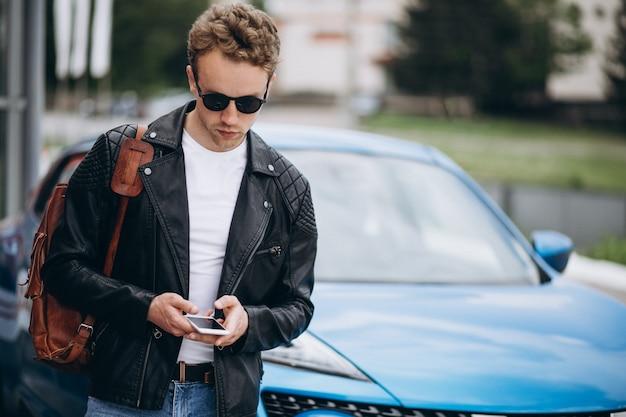 Jovem bonito usando telefone pelo carro Foto gratuita