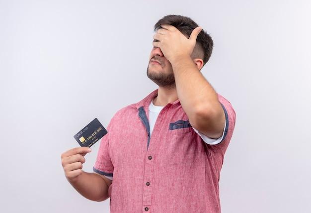 Jovem bonito vestindo uma camisa polo rosa com a palma da mão virada segurando um cartão de crédito em pé sobre uma parede branca Foto gratuita