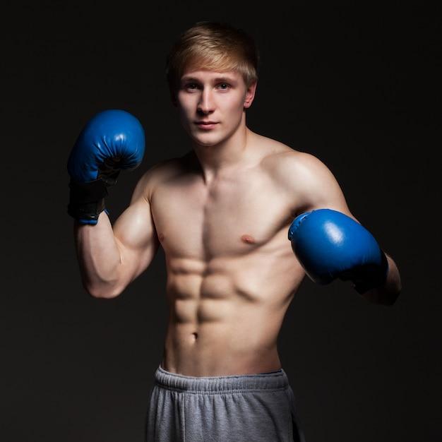 Jovem boxeador bonito em luvas azuis Foto gratuita