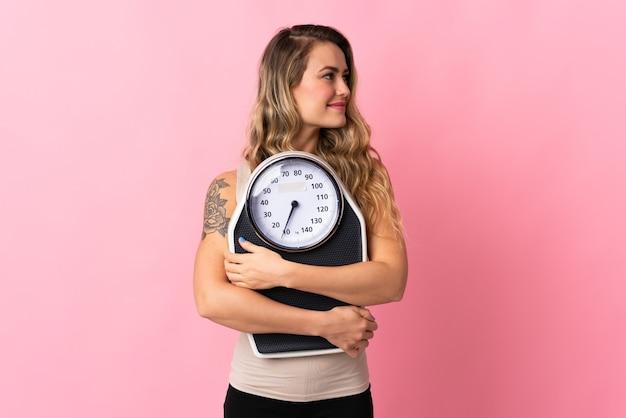 Jovem brasileira isolada em rosa com balança e olhando de lado Foto Premium