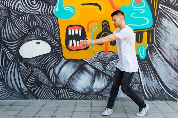 Jovem breakdancer dançando contra texturizado pintado Foto gratuita