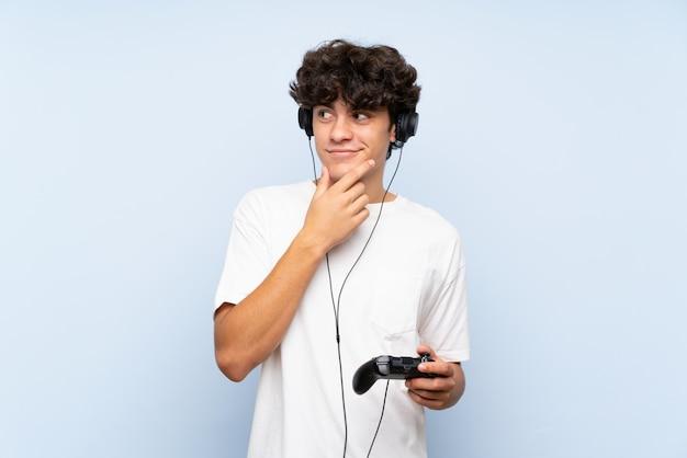 Jovem brincando com um controlador de videogame sobre parede azul isolada, pensando uma idéia Foto Premium