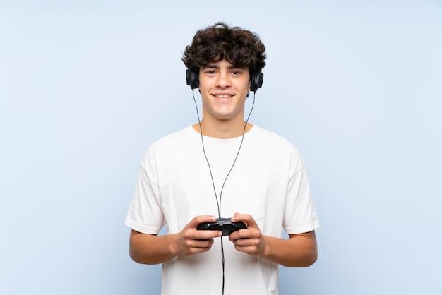 Jovem brincando com um controlador de videogame sobre parede azul isolada, sorrindo muito Foto Premium
