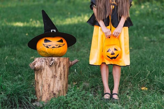Jovem bruxa e jack-o-lanterna em pé na floresta no dia das bruxas Foto gratuita
