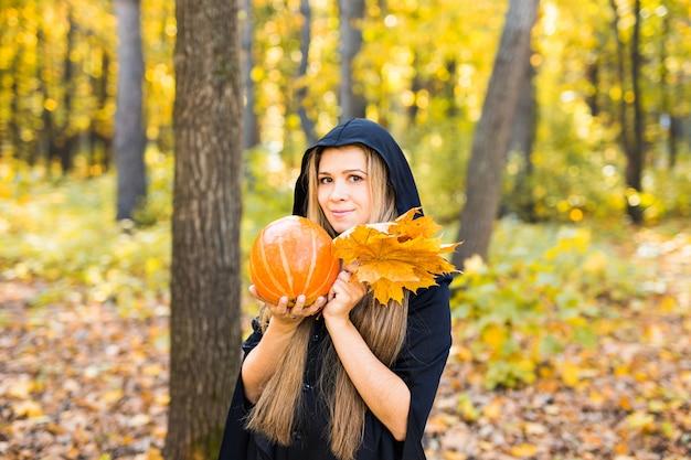 Jovem bruxa em uma floresta. dia das bruxas Foto Premium