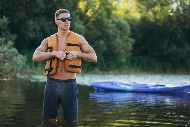 Jovem, caiaque no rio Foto gratuita