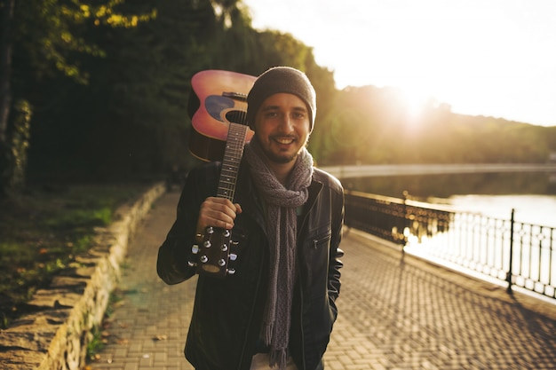 Jovem caminha à beira do lago e segurando o violão Foto gratuita
