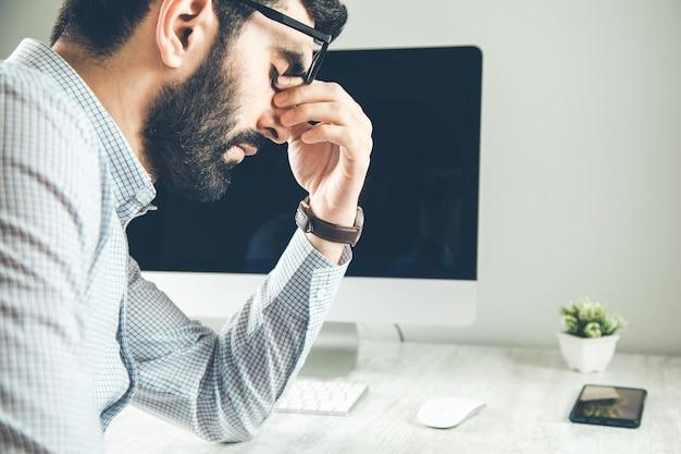 Jovem cansado sente dor e fadiga ocular segurando óculos esfregando olhos irritados e secos, cansado do trabalho no computador Foto Premium