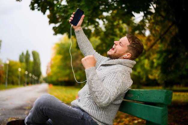 Jovem cantando em um banco no parque Foto gratuita