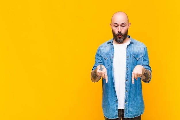Jovem careca e barbudo com a boca aberta apontando para baixo com as duas mãos, parecendo chocado, pasmo e surpreso Foto Premium