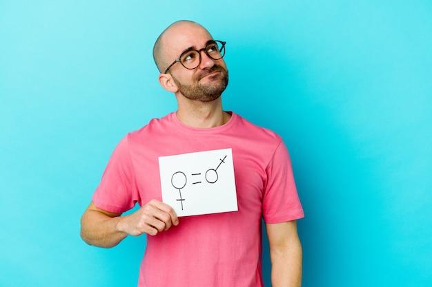 Jovem careca segurando um cartaz de igualdade de gênero isolado na parede amarela, sonhando em alcançar objetivos e propósitos Foto Premium