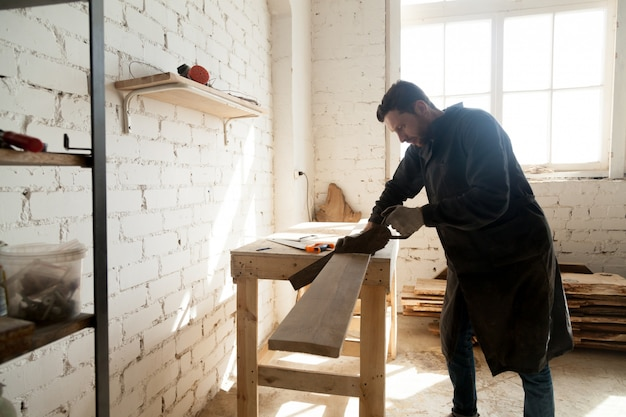 Jovem carpinteiro cortando placa de madeira com serra de mão na oficina Foto gratuita
