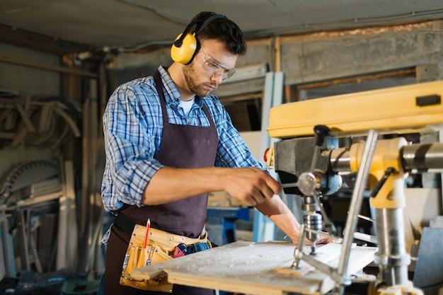 Jovem carpinteiro focado no trabalho Foto gratuita