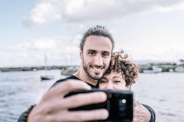 Jovem casal abraçado pelo ombro, fazendo um selfie com o porto e o mar fora de foco Foto gratuita