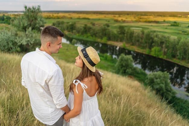 Jovem casal abraçando no campo e olhando um ao outro Foto Premium