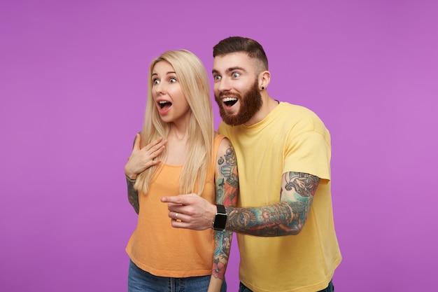 Jovem casal adorável tatuado de olhos abertos olhando surpreso para o lado com a boca aberta enquanto está de pé sobre um fundo roxo em roupas casuais laranja Foto gratuita