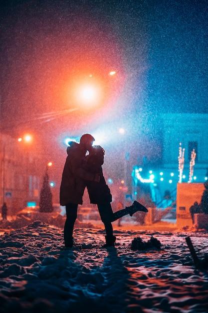 Jovem casal adulto nos braços um do outro na rua coberta de neve Foto gratuita