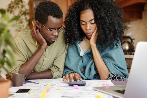 Jovem casal africano estressado não suporta a tensão da crise financeira, parecendo infeliz e frustrado, sentado à mesa da cozinha com calculadora, tentando economizar algum dinheiro cortando despesas domésticas Foto gratuita