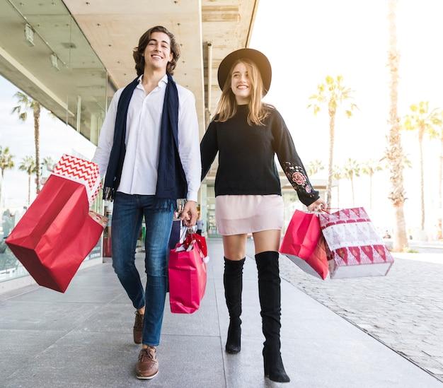 Jovem casal alegre andando com sacolas de compras Foto gratuita