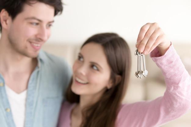 Jovem casal alegre segurando as chaves da casa nova Foto gratuita