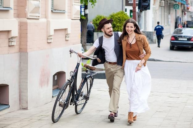 Jovem casal andando com bicicleta e abraçando Foto gratuita