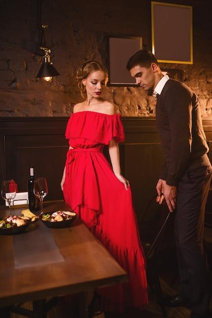 Jovem casal apaixonado em restaurante, encontro romântico. mulher elegante em vestido vermelho e seu homem jantando Foto Premium