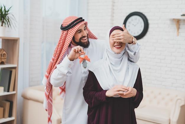 Jovem casal árabe em movimento homem fecha os olhos para a esposa Foto Premium