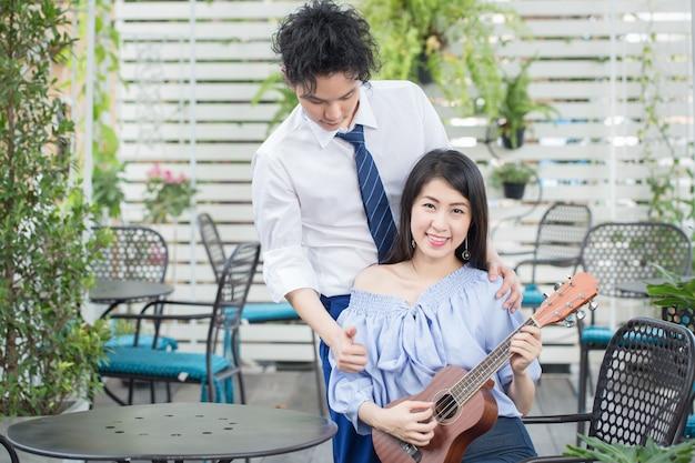 Jovem casal asiático apaixonado tocando violão, adolescente feliz raça mista Foto Premium
