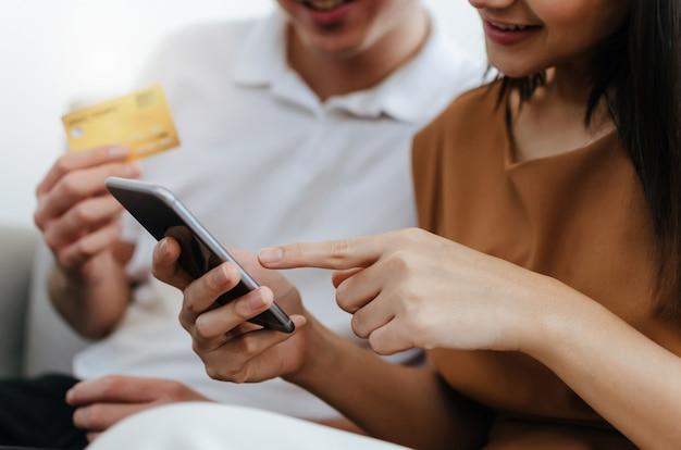 Jovem casal asiático digitando o código de segurança no telefone móvel esperto e pagando o cartão de crédito no sofá em casa, escritório Foto Premium