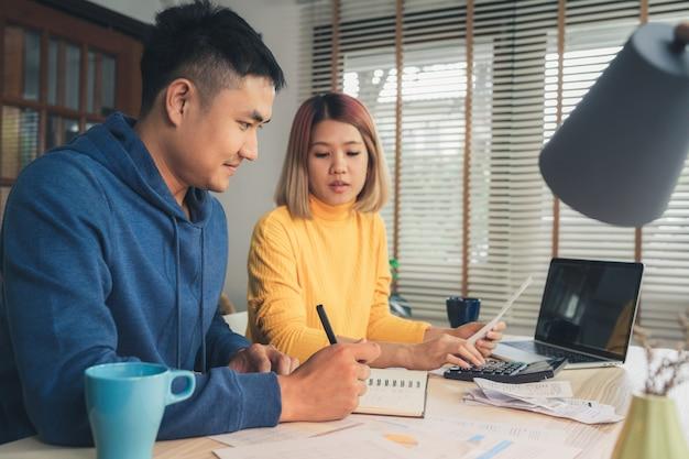 Jovem casal asiático gerenciando finanças, revendo suas contas bancárias usando o computador portátil Foto gratuita
