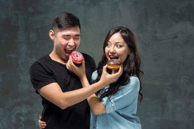 Jovem casal asiático gosta de comer doce rosquinha colorida Foto gratuita