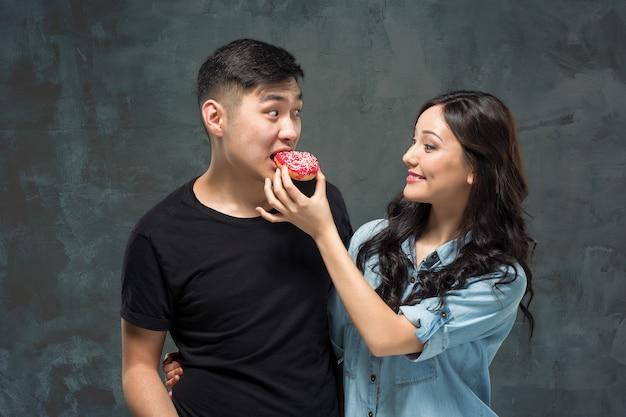 Jovem casal asiático gosta de comer rosquinhas doces e coloridas no fundo cinza do estúdio Foto gratuita