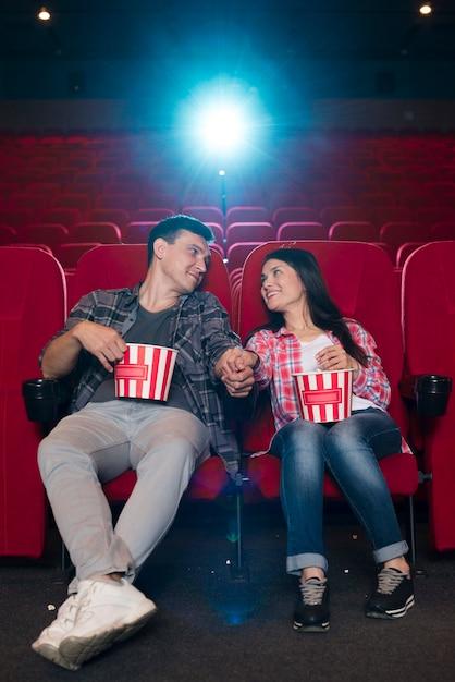 Jovem casal assistindo filme no cinema Foto gratuita