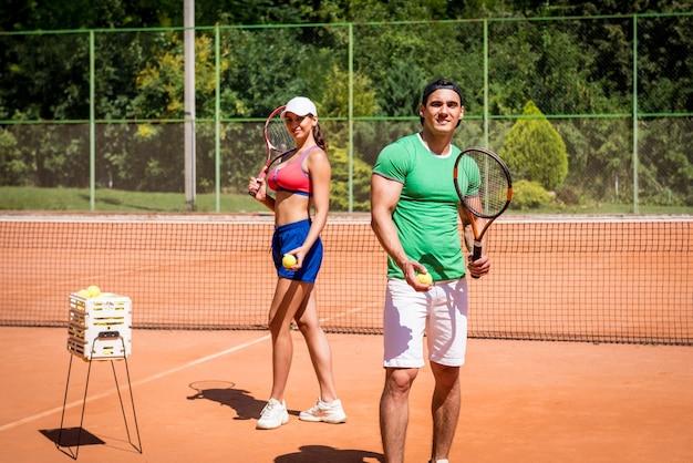 Jovem casal atlético jogando tênis na quadra. Foto Premium