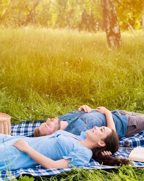 Jovem casal atraente relaxante no piquenique na natureza Foto gratuita